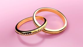 Pair of golden wedding rings connected together forever with carved love words that symbolize love and eternal relationship. Pair of golden wedding rings that Royalty Free Stock Photos