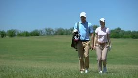 Pair of golfers with clubs bag communicating during course walk after game hobby. Stock footage stock video footage