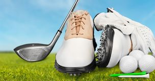 Pair of golfing shoes and a golf club on green stock images