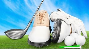 Pair of golfing shoes and a golf club on green royalty free stock photo