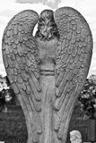 A Pair of Granite Angel Wings. Granite Angel Wings Overlooking a Grave in a Cemetery royalty free stock photos