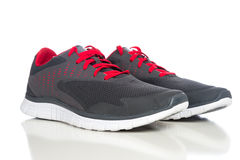 A pair of gray running shoes with red shoelaces on a white backg Stock Photo