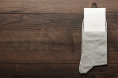 Pair of gray socks with blank packing. On the wooden table royalty free stock image