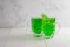Pair of green beer glasses with splash. On a white wooden background Royalty Free Stock Photo
