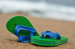 A pair of green and blue flip flops on the beach Royalty Free Stock Photography