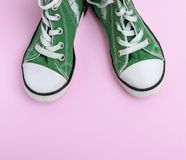 Pair of green children`s shoes on a pink background. Top view royalty free stock photos