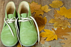 Pair of green leather boots and yellow leaves Stock Photos