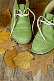 Pair of green leather boots and yellow leaves Royalty Free Stock Images