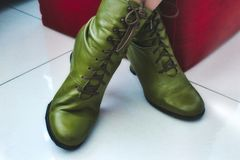 A pair of green leather women`s boots with shoelaces and heels. A pair of ankle-high green leather women`s boots with shoelaces and heels stock image