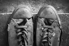 Pair of grungy sneakers standing on concrete. Pair of old sneakers standing on concrete stairs, closeup top view. Black and white retro stylized photo stock photo
