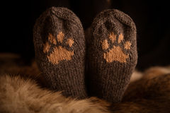 Pair of a hand knitted woolen socks with a cat paw pattern. On fur background royalty free stock images