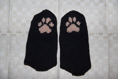 Pair of a hand knitted woolen socks with a cat paw pattern Royalty Free Stock Photo