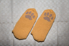 Pair of a hand knitted woolen socks with a cat paw pattern Stock Image