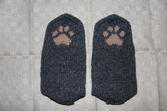 Pair of a hand knitted woolen socks with a cat paw pattern. On linen background stock photos