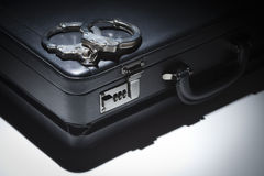 Pair of Handcuffs and Briefcase Under Spot Light Royalty Free Stock Photos