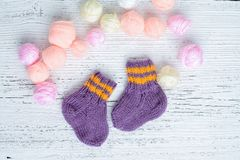Pair of handmade woolen socks for newborn. Pair of small and cute handmade woolen socks for newborn, on white wooden background royalty free stock images