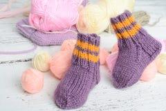Pair of handmade woolen socks for newborn. Pair of small and cute handmade woolen socks for newborn, on white wooden background stock image