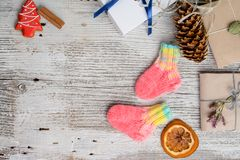 Pair of handmade woolen socks for newborn. Pair of small and cute handmade woolen socks for newborn, on white wooden background stock photo