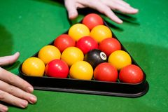 A pair of hands setting up a triangle in pool. With a `c broken j Stock Photo