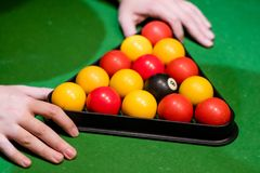A pair of hands setting up a triangle in pool. A pair of hands setting up a triangle in pool with a `c broken j Stock Image