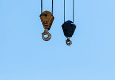 Pair of hanging industrial crane hoists on pale blue sky. Stock Photography