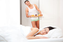 Pair having breakfast in bed. Husband serving breaktfast for girlfriend to bed at home Royalty Free Stock Photos
