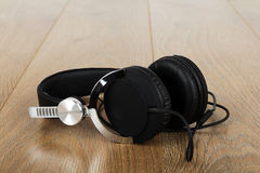 Pair of headphones on a rustic wooden surface Royalty Free Stock Photo