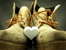 Pair of heavy military boots and white heart. Royalty Free Stock Photos
