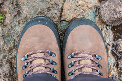 A pair of hiking boots. A pair of brown hiking boots on wet rocks in the outdoors Royalty Free Stock Photos