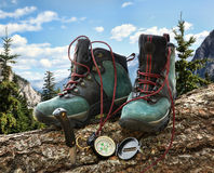 Pair of hiking boots with compass on fallen tree royalty free stock images