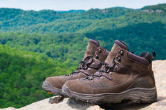 Pair of hiking boots  in front of mountain forest  Royalty Free Stock Image