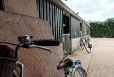 Pair of his and hers bicycles seen leaned against a wall at a horse livery yard. Royalty Free Stock Images
