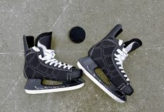 Pair of hockey skates with puck on a ice rink. Stock Images