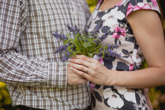 Pair is holding hands and bouquet. Close-up shot of pair holding hands and huging with violet bouquet Stock Photography