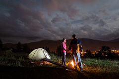 Pair holding hands, standing near camp, looking at each other Royalty Free Stock Photo