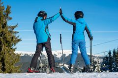 Pair holding hands standing with skis on mountain top Stock Images