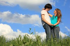 Pair holds each other in  grass against sky Stock Photos