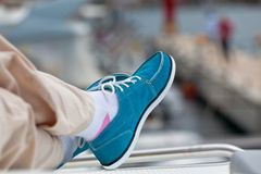 A pair of human legs in pants and bright blue topsiders Royalty Free Stock Photos