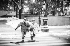 Pair in a hurry crossing the street royalty free stock image