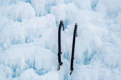Pair of ice axes on blue wavy ice Stock Photos