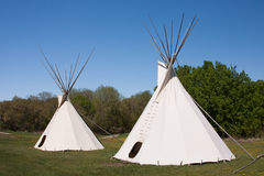 Pair of Indian Teepees. A small group of teepees in a meadow surrounded by forest. Teepees were traditional housing for Native Americans in Great Plains and stock photography