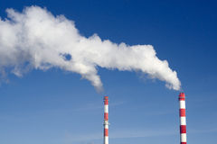 Pair of industrial chimneys with lot of smoke. On a blue sky royalty free stock photography