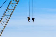 Pair of industrial crane hoists on cables near truss. Royalty Free Stock Images