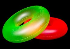 Pair of Inflatable Round Pool Tubes. Isolated on black royalty free stock photo