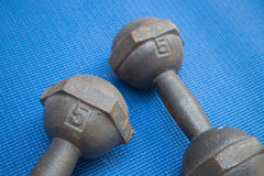 Pair of iron dumbbell 5 kilograms on blue yoga mat Royalty Free Stock Images
