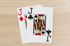 Pair of jacks - casino playing poker cards. Pair of jacks - winning hand of gambling casino poker playing cards on a table stock image