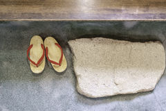 Pair of japanese traditional shoe on stone floor. With stone and wood step Royalty Free Stock Photo