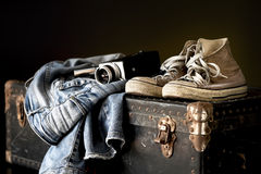 Pair of jeans sneakers and movie camera. Pair of jeans sneakers and old movie camera on a vintage suitcase royalty free stock photo