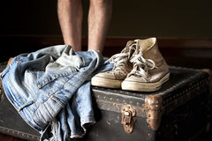 Pair of jeans and sneakers on suitcase Royalty Free Stock Image