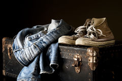 Pair of jeans and sneakers. On a vintage suitcase royalty free stock image